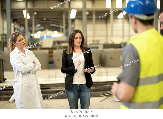 Female boss briefing her coworkers in factory