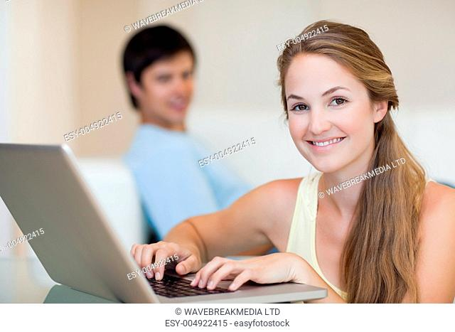 Woman using a laptop while her husband is sitting on a couch