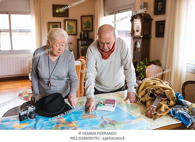 Elderly couple planning a trip on a map. Barcelona, Spain