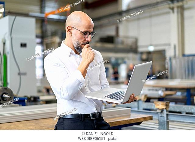 Focused businessman using laptop in factory