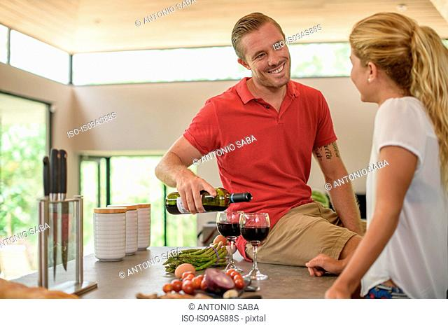 Couple preparing food and pouring red wine in kitchen