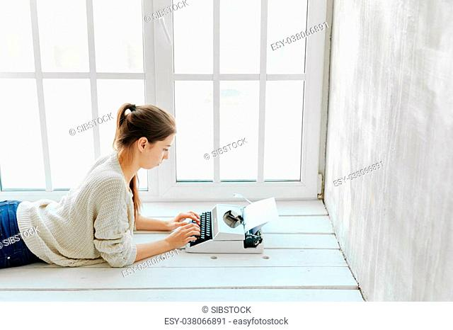 Unidentified woman's hand typing on retro typing machine