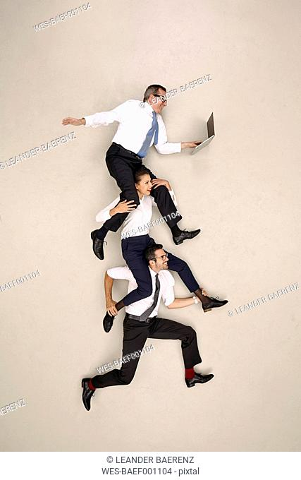 Businessman carrying his two male colleagues on his shoulders