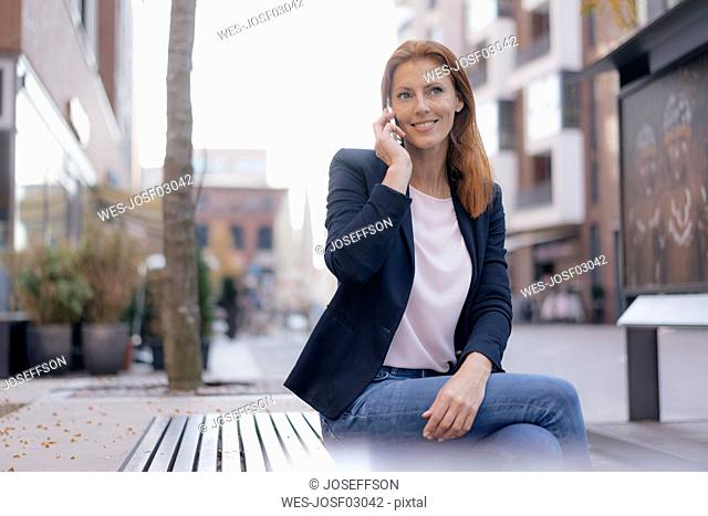 Smiling businesswoman on cell phone sitting outdoors in the city