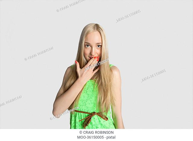 Portrait of surprised teenage girl with hand over mouth over gray background