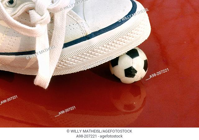 white sports shoe with tiny football