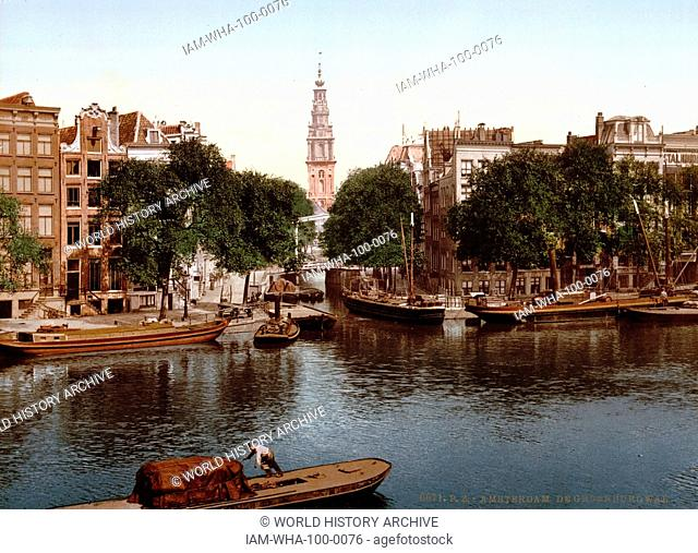 photomechanical print dated to 1900, depicting the Groen Burgwal (canal), Amsterdam. The Munttoren ('Mint Tower') can be seen in the distance