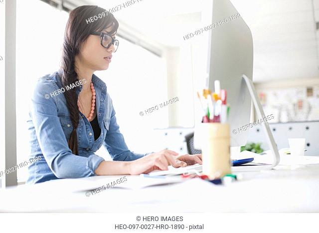 pretty, asian professional at keyboard