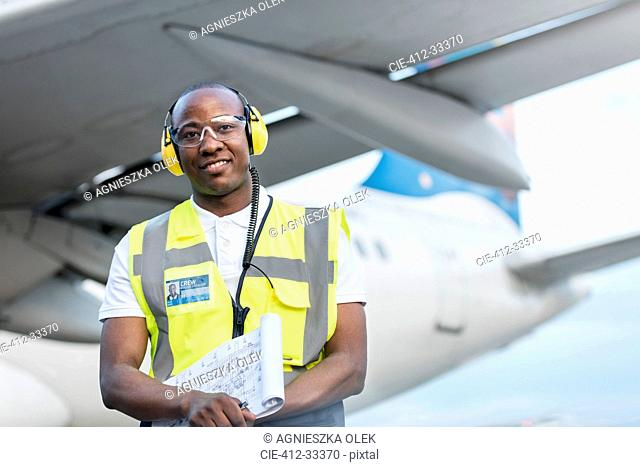 Air traffic controller with clipboard under airplane on airport tarmac