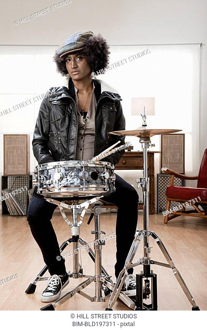 Mixed race woman playing drums
