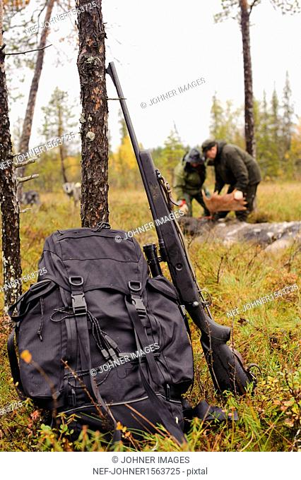 Rifle and backpack leaning on tree trunk, hunters in background