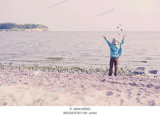 Germany, Mecklenburg-Western Pomerania, Ruegen, Boy on shingle beach throwing stones in the ocean