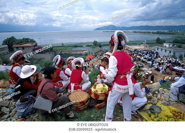 Group of Bai ethnic minority girls in traditonal costume above a market with the sea in the distance