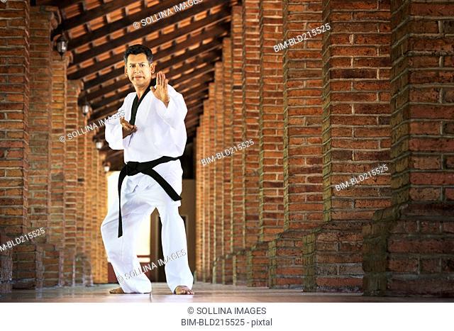 Hispanic man practicing martial arts in hallway