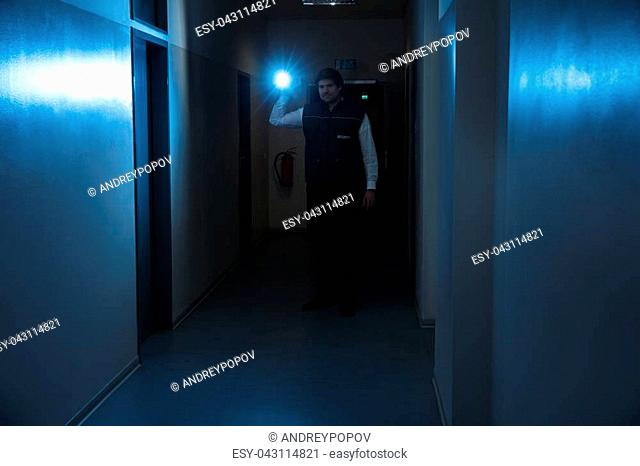 Male Security Guard Holding Flashlight Standing In Corridor Of The Building