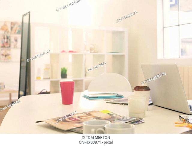 Laptop, coffee cups and fashion magazines on table in office