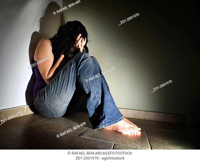 Depressed young woman sitting on the floor at home suffering from a severe depression