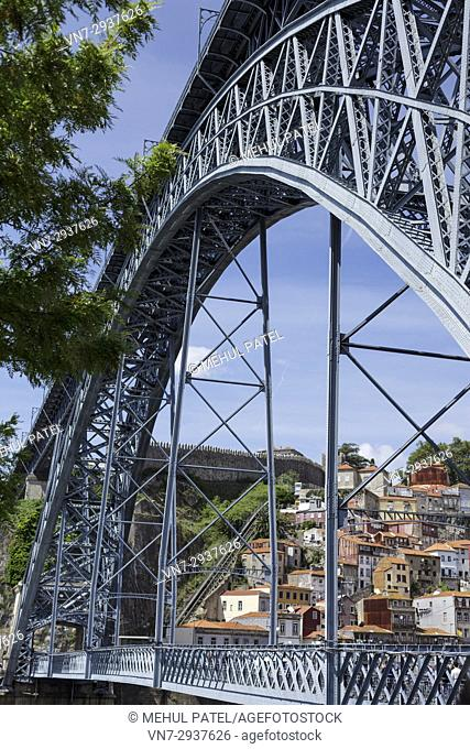 Ponte Luis I (Dom Luis I bridge) with view of funicular and the Muralha Fernandina in the distance - Porto, Portugal. The metal arch bridge connects the cities...