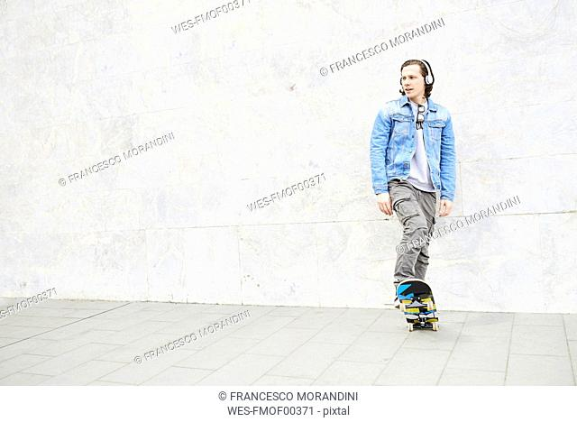 Young man stepping on skateboard, looking away
