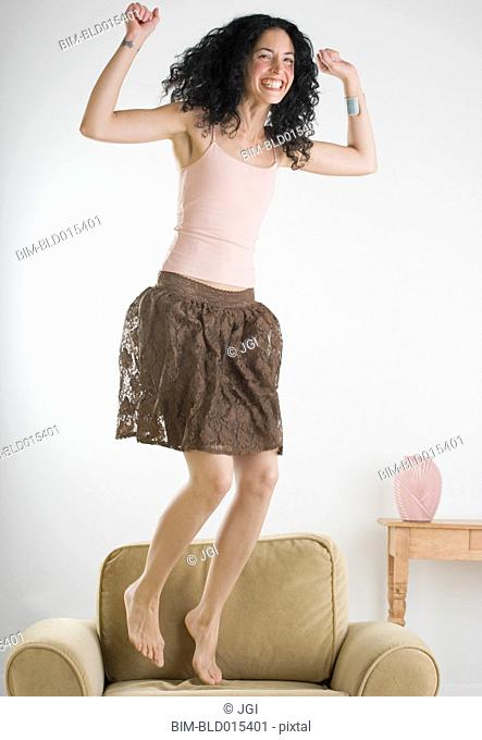 Young woman jumping on the couch