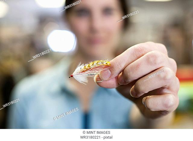 Close up of a hand holding a fly in a fly shop. The fly is used to catch trout and salmon while fly-fishing