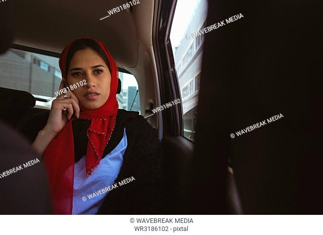 Hijab woman talking on mobile phone in the car