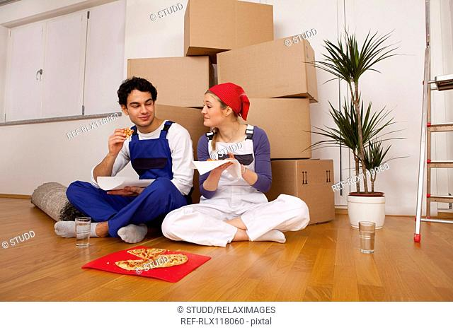 couple new home moving in eating pizza lunch break
