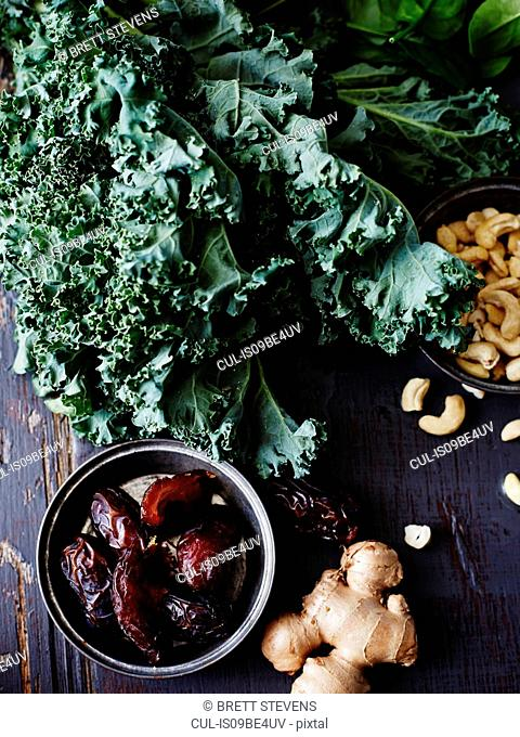 Still life of kale, dates, cashews and fresh ginger, overhead view