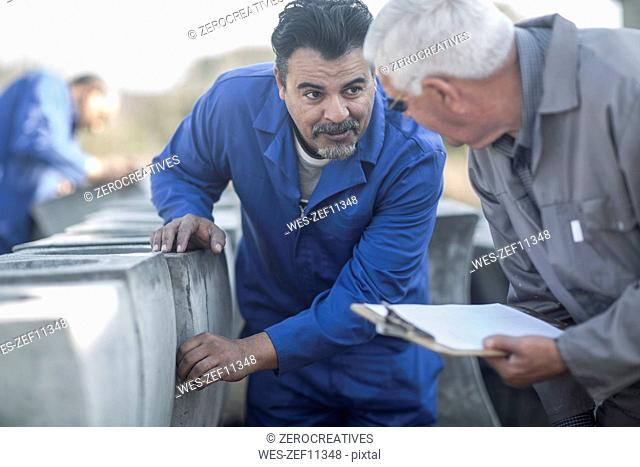 Two men talking at industrial pot factory