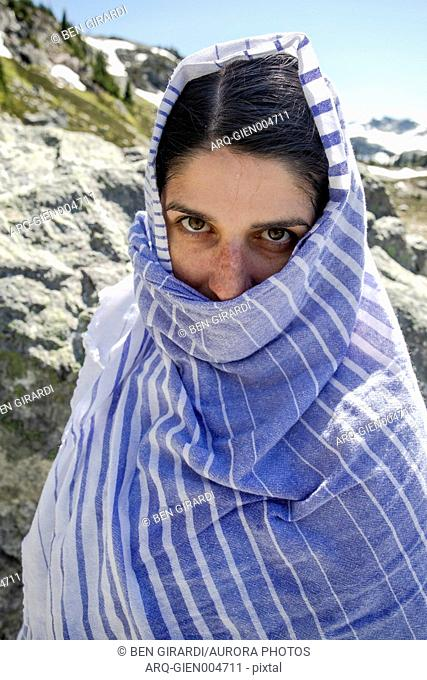 Outdoor portrait of a woman wrapped in a towel after swimming in a lake in mountains