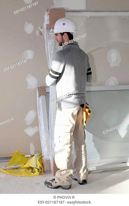 Man installing plaster board divide
