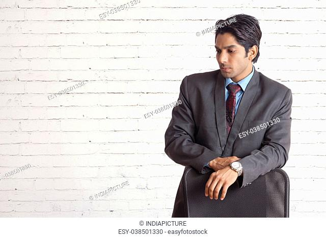 Portrait of a young business man looking depressed from work