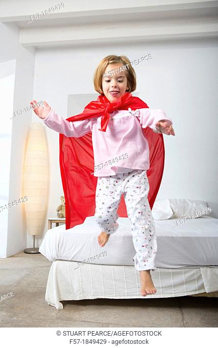 Four year old girl jumping off the bed in a red cape
