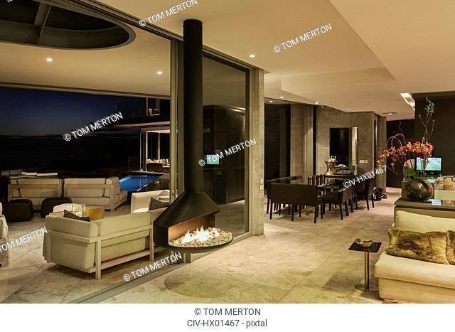 Illuminated luxury modern home showcase interior with hanging fireplace