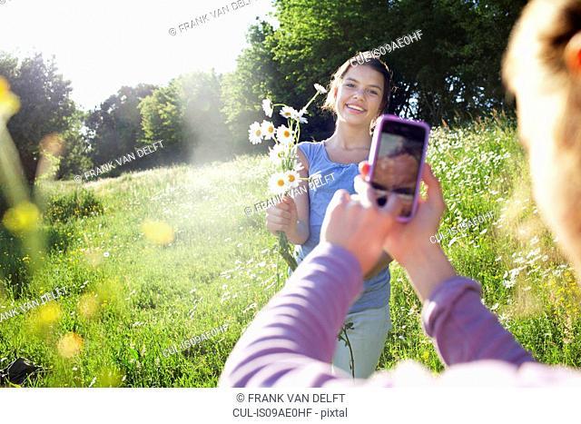 Girl taking photograph of girl picking flowers