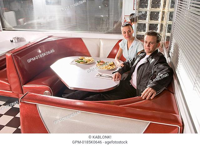 Young couple sitting at table in old-fashioned diner booth wearing 1950s style clothing