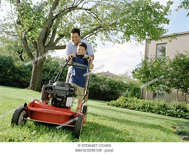 Father and son mowing the lawn together