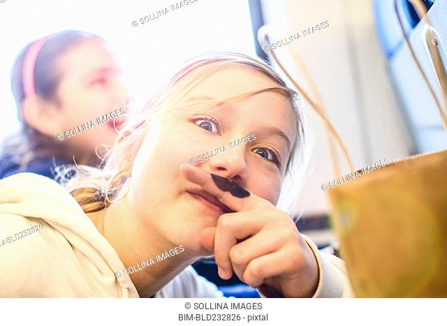 Caucasian girl with mustache on finger