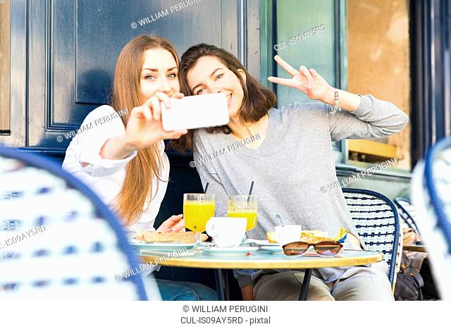 Two young female friends taking smartphone selfie at sidewalk cafe, Paris, France