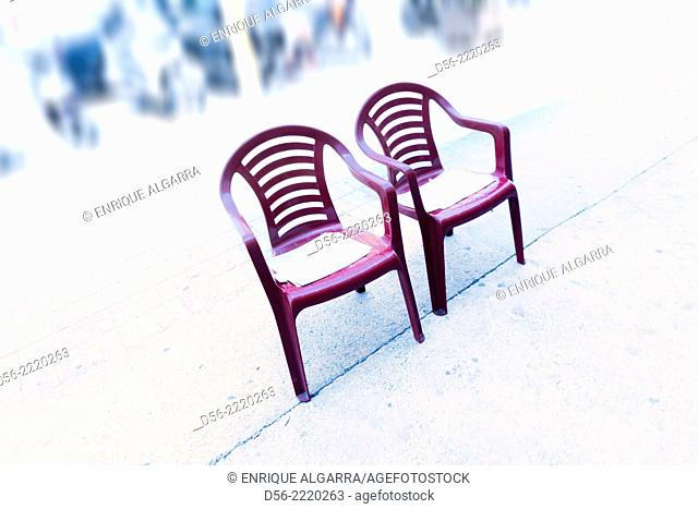 two plastic chairs front a chinese commerce, Benidorm, Alicante province, Spain