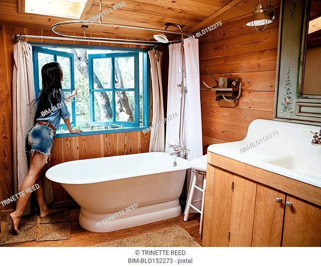 Chinese woman opening window of rustic bathroom