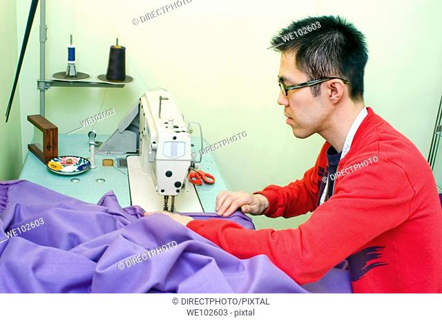 Stock Photo of Young Asian Man Tailor Working on Curtains in home Studio