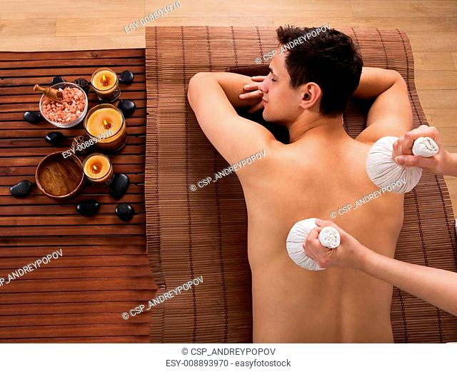 Young Man Receiving Massage With Stamps In Spa