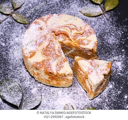 round dessert cheesecake with pumpkin on black background, top view