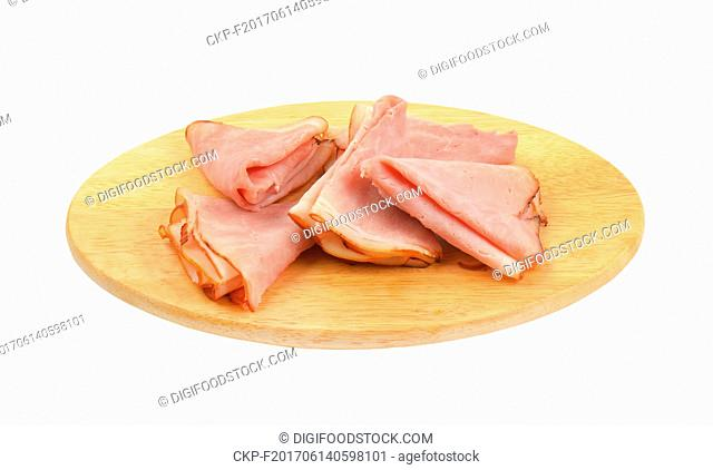 slices of pork ham on oval wooden cutting board
