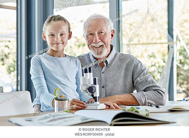 Grandfather supporting granddaughter in nature studies