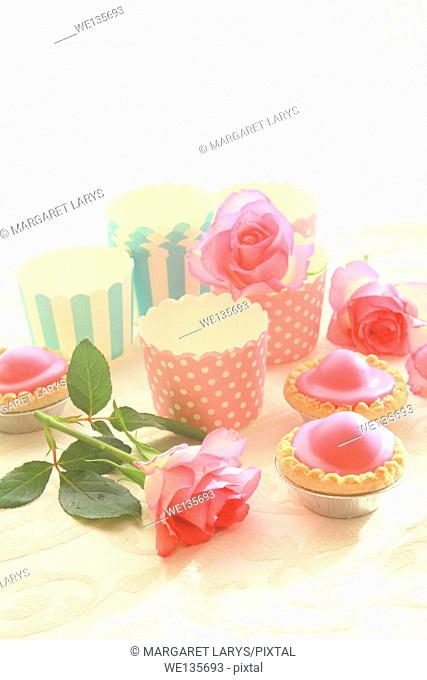 Emepty round muffin cups and pink cakes
