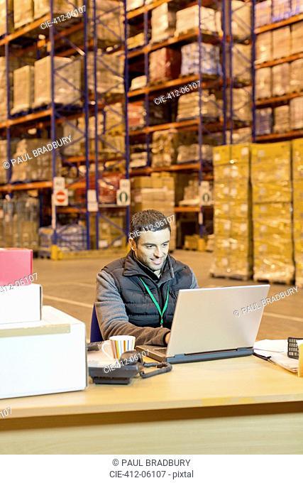 Worker using laptop in warehouse