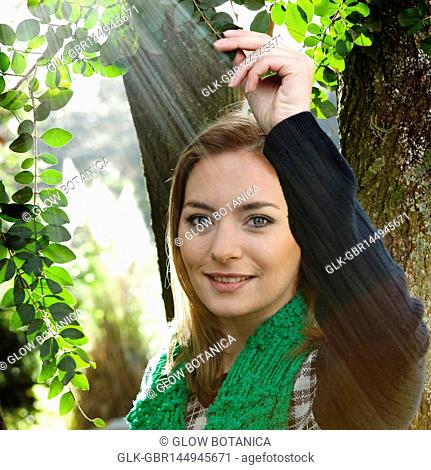 Portrait of a woman holding a branch and smiling