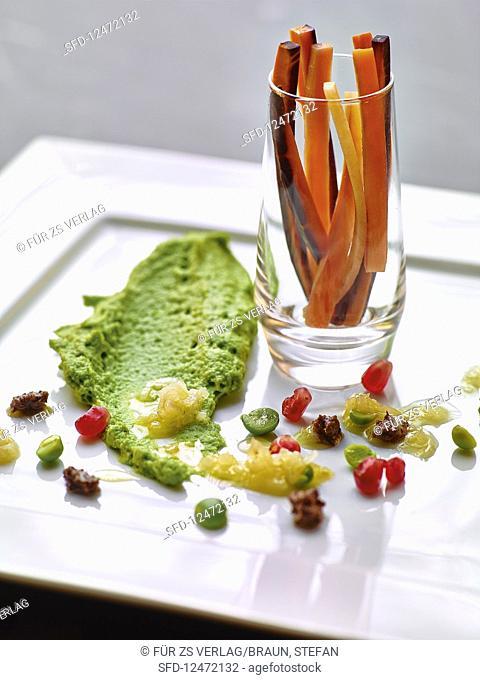 Mushy peas with olive pesto, pomegranate seeds and carrot sticks